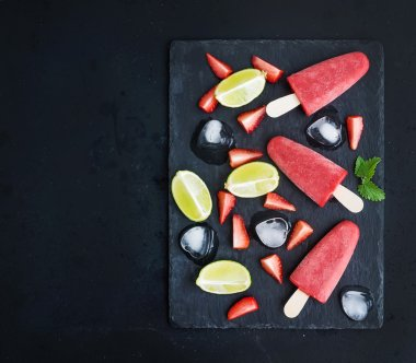 Strawberry and lime ice-creams or popsicles with fresg cut berries, citruses, ice cubes, melissa leaves on black slate tray over dark grunge backdrop, top view