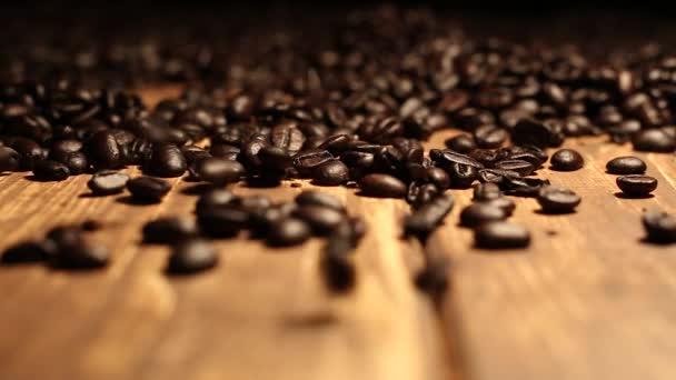 Roasted coffee beans falling on wooden table covered with coffee beans
