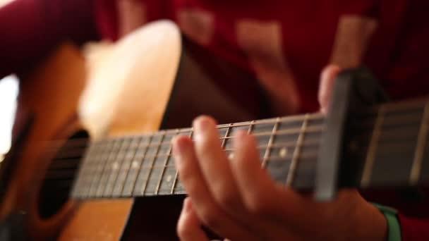 Muž v červeném svetru hraje na akustickou kytaru v interiéru, detailní pohled na široký otevřený otvor