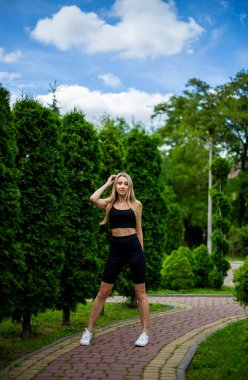 Young beautiful sporty blonde woman in a black T-shirt and in black tight sports shorts in good shape posing in front of green trees and bushes in nature