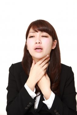 young Japanese businesswoman having throat pain