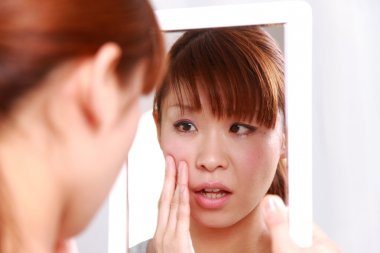 Young Japanese woman worries about dry rough skin