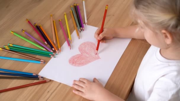 egy kisgyerek keze rajzoljon egy szívet piros ceruzával egy fehér papírra.