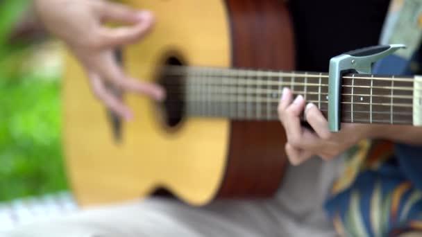women practice acoustic guitar in the garden