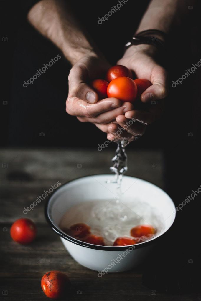 Washing tomatoes. Male chef washing tomatoes. Tomatoes in hands