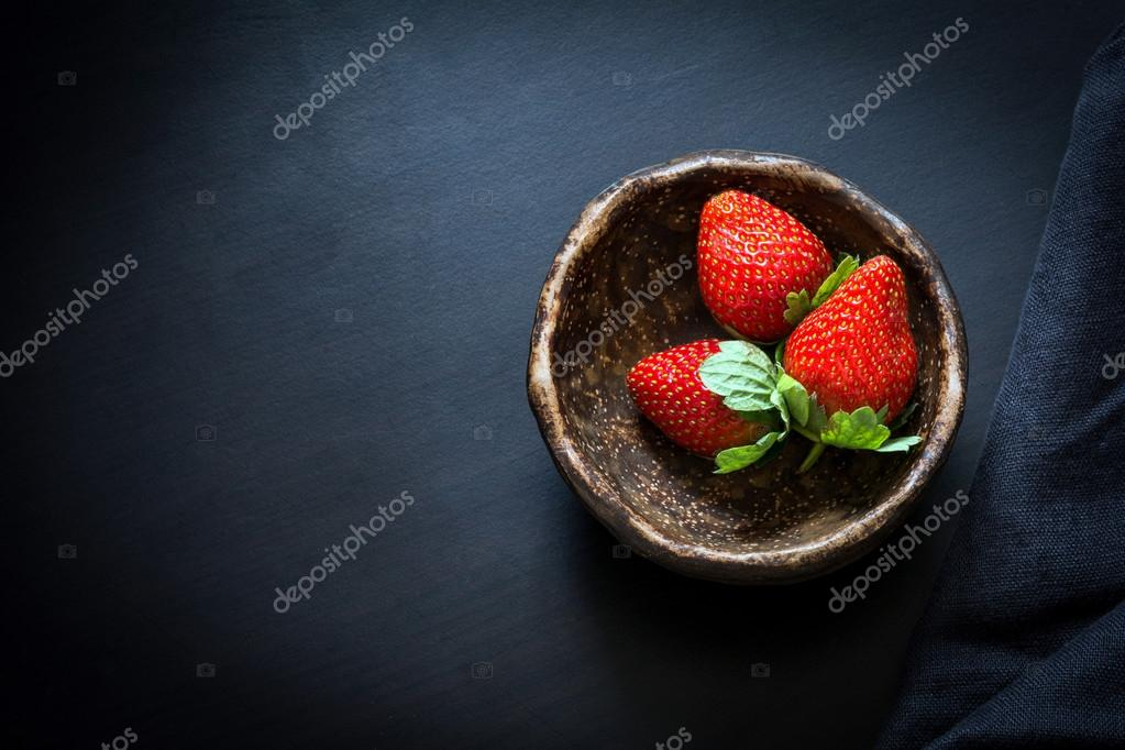 Strawberries in bowl on black background, top view
