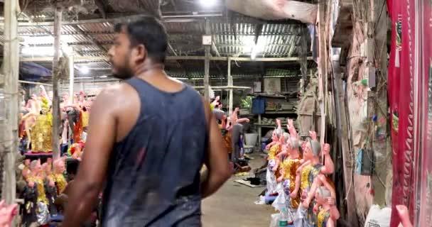 Kumartuli, Kalkutta, Indien - 17. September 2020- Dutzende von Vishwakama-Idolen in einer Werkstatt in Kumortuli, bereit, ausgeliefert zu werden, während ein Mann vorbeiläuft, um den Fortschritt zu überwachen. Größtes Hindu-Fest