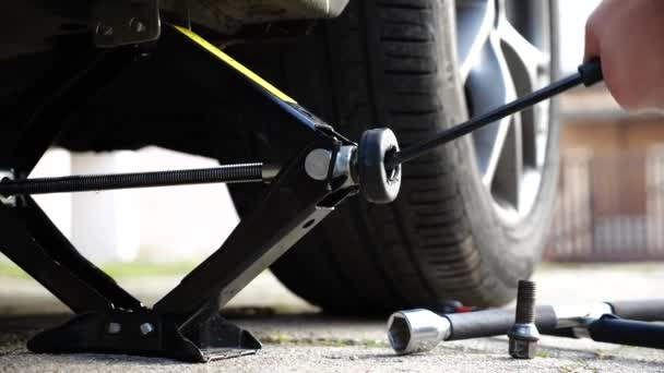 Měním kolo nebo pneumatiku. Muž používající auto jack k odšroubování a výměně kola. letní nebo zimní výměna pneumatik na dvorku.