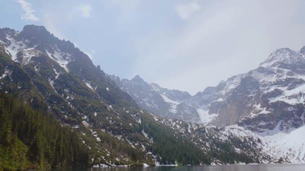 Vysoké skalnaté hory a křišťálově čisté tyrkysové panorama jezera. Tatry, jezero v horách pokryté sněhovým panoramatickým výhledem.