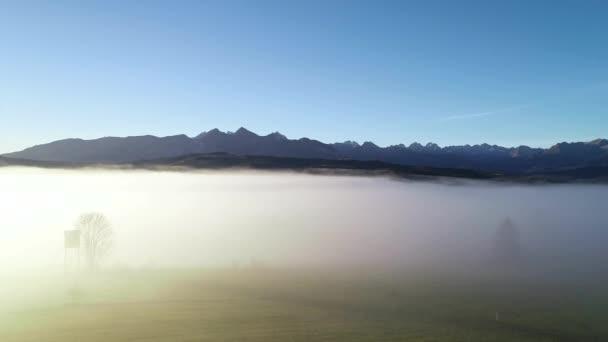 Letecký pohled na podzimní hory. Slunečné mlhavé ráno, epická alpská krajina, les pokrytý mlhou. Vysoký panoramatický výhled na Tatry v Polsku, v Evropě. Idylická ranní scéna. Hyperlapse