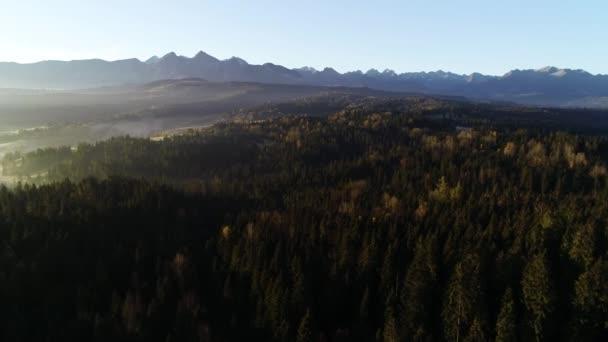 Letecký pohled na horskou krajinu s ranní mlhou, Tatry vysoké hory ve slunečném ránu po východu slunce. Dronové záběry zamlženého lesa a magické alpské scenérie