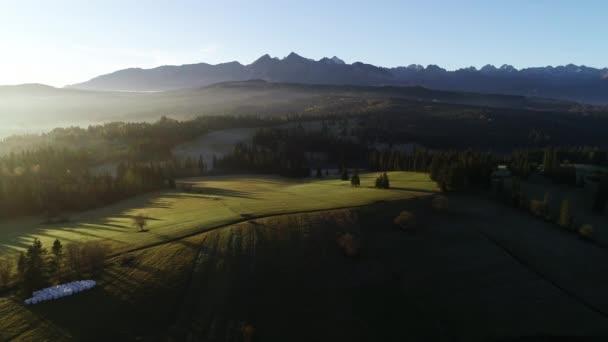 Letecký pohled na podzimní hory. Slunečné mlhavé ráno, epická alpská krajina, les pokrytý mlhou. Vysoký panoramatický výhled na Tatry v Polsku, v Evropě. Idylický úsvit.