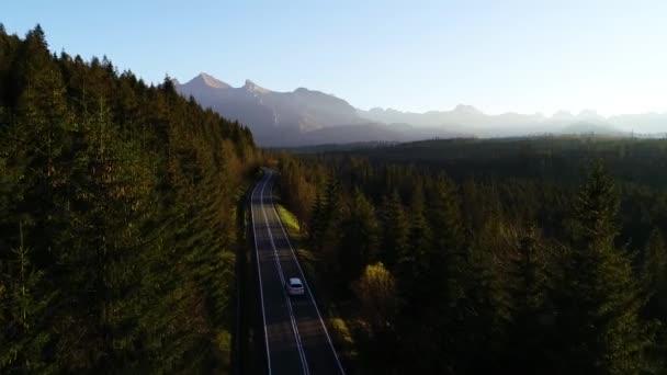 Letecký pohled na horské zvrácené silnice a luxusní SUV auto jedoucí do hor. Krásný podzim v horách a slunná čistá cesta přes pestrobarevný les