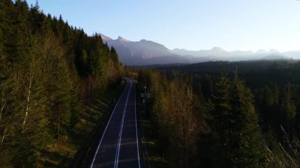 Letecký pohled na pokroucenou horskou cestu a skalnatou řeku. Krásný teplý podzim v horách a slunná čistá cesta přes pestrobarevný les. Epické drone záběry dálnice v divoké horské scenérie.