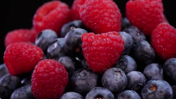 Raspberries and blueberries rotating on a black background close up view. Fresh, firm and tasty berries with mint in 4K. Raw vegan summer snacks, forest berries.