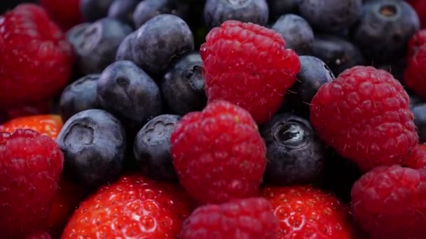 Strawberries, raspberries and blueberries rotating on a black background. Fresh, organic forest fruits in 4K. Raw vegan summer snack close up.