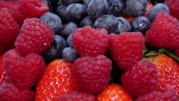 Strawberries, raspberries and blueberries rotating on a black background. Fresh, organic forest fruits in 4K. Raw vegan summer snack.