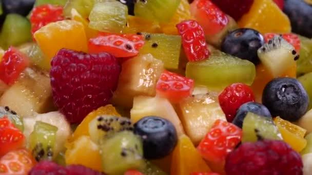Színes gyümölcssaláta forgó fekete alapon 4K. Friss és ízletes gyümölcsök, narancs, alma, bogyós gyümölcsök, gránátalma, kivi, anananász, málna, áfonya és eper közelsége