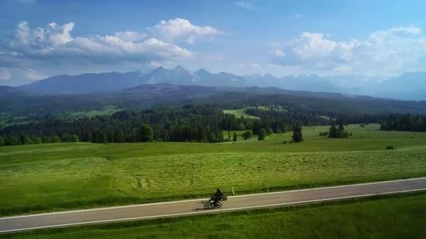 Letecký pohled na horskou silnici a dva motocyklisté jedou po prázdné silnici. V pozadí epického širokého pohoří. Koncept: Dovolená v horách, výlet, cestování.