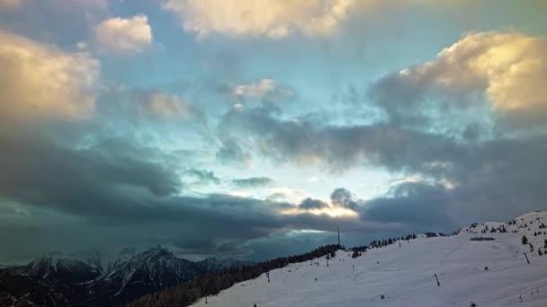 Včas tančících mraků nad horami během západu slunce. Panoramatický výhled na alpské svahy. Lidé lyžují ve švýcarských Alpách. Bettmeralp. Kanton Valais. Švýcarsko.