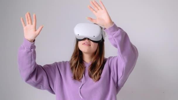 Junge lächelnde Kaukasierin mit VR-Headset, gestikulierend und in virtueller Realität isoliert auf weißem Hintergrund aufblickend.