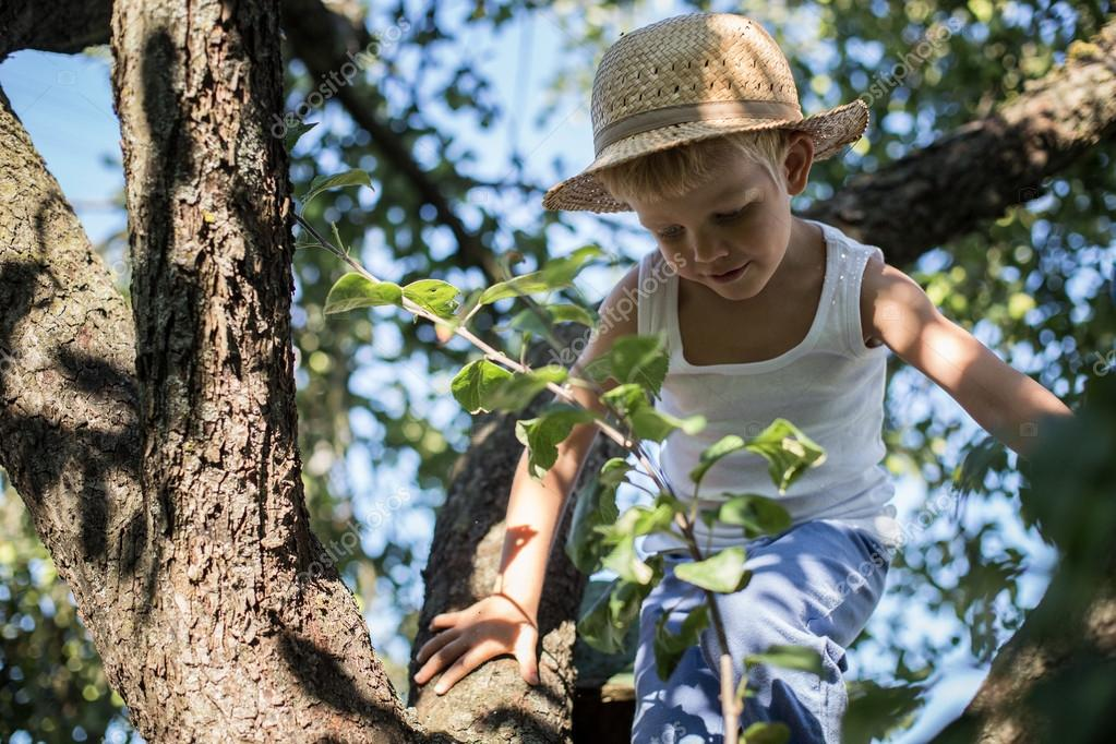 Little boy with straw hat climbing a tree