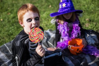 Boy and girl wearing halloween costume with candies. Skeleton. Witch