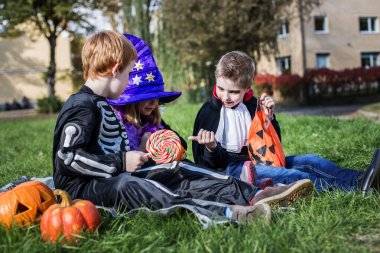 Three young friends sharing Halloween candies