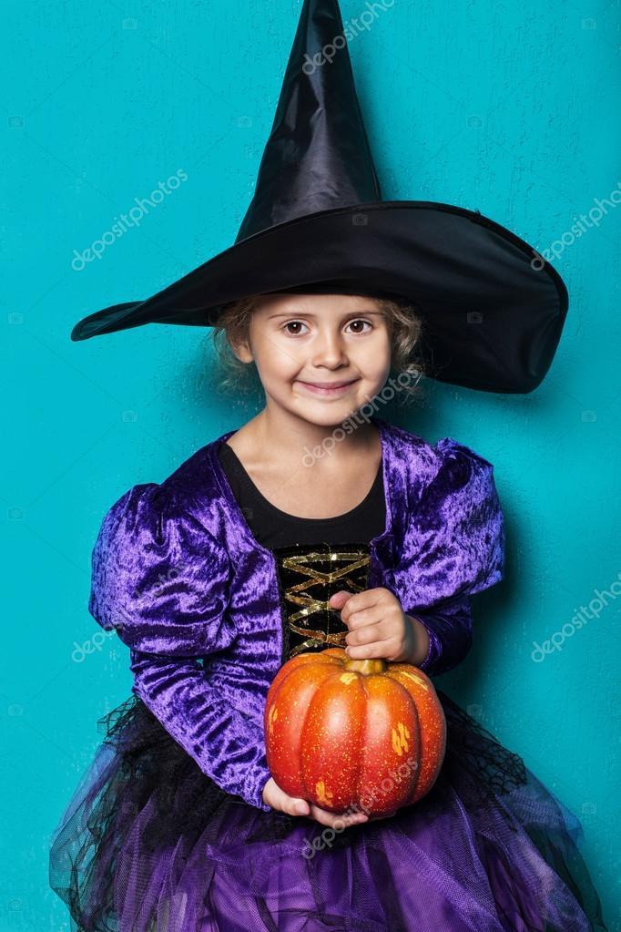 Porträtt av liten flicka i svart hatt och häxa kläder med pumpa. Halloween.  Fairy 50b6caf732d1a
