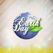 Fényképek Earth Day background with the words, world globe and green leaves. Wooden texture. Vector illustration
