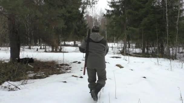 Hunter egy havas erdőben fegyverrel és vadászkutyákkal. Téli vadászidény Európában.