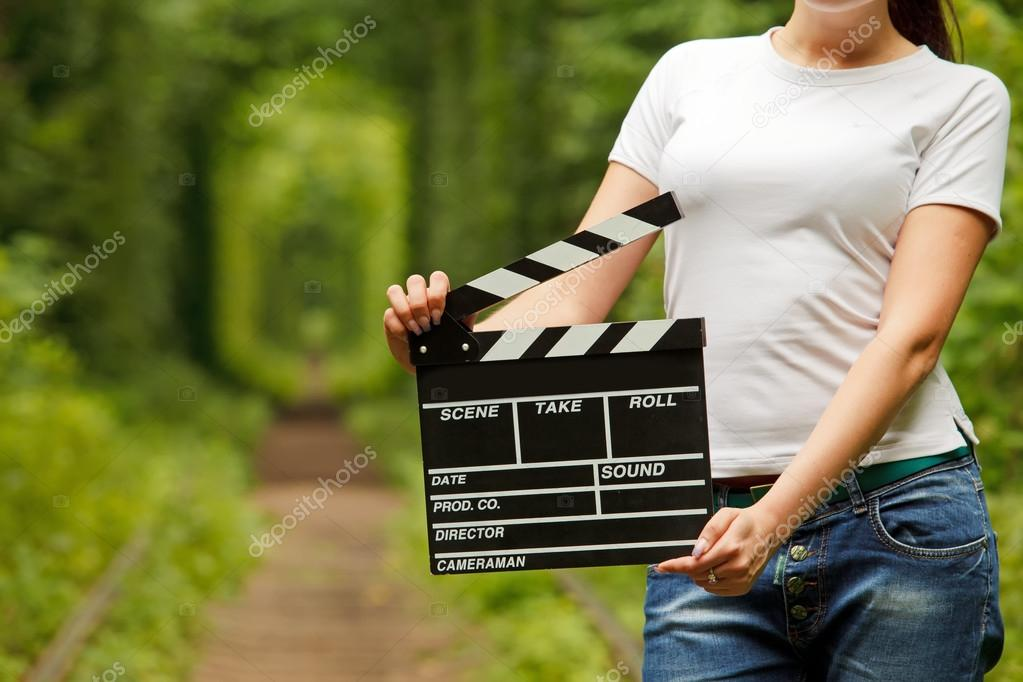 Woman holding clapper board in her hands. tunnel of love in ukra