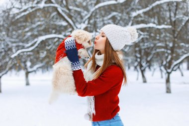 Stylish woman holding a dog and kisses him
