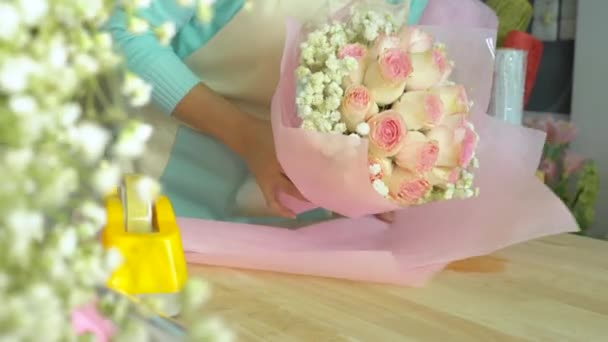 Flower shop, arranging bouquet, hand of florist pink wrapping paper around pink rose bouquet