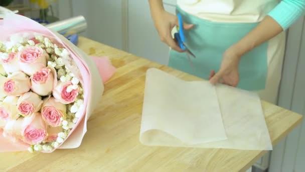 Virágbolt, csokor, kéz a virágárus, vágás, és ezen a környéken: rózsaszín rózsa csokor fehér csomagolás csomagolópapír megszervezése