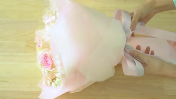 Arranging bouquet, hand of florist tying ribbons around pink rose bouquet