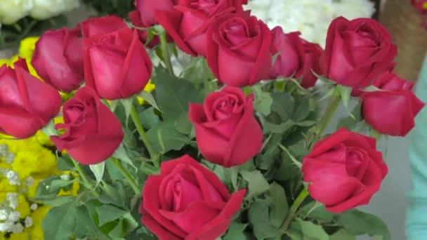Flower shop, hand of florist arranging red roses