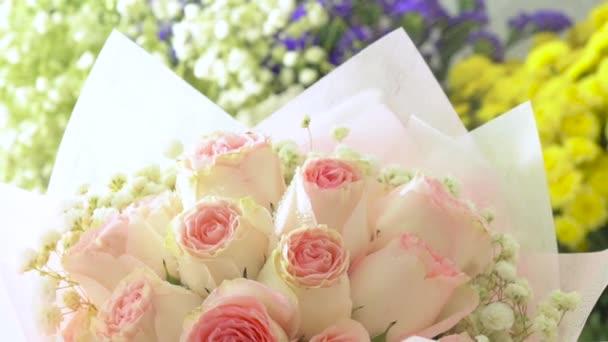 Various flowers, pink rose bouquet, florist spraying water on bouquet