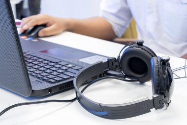 Man hand using keyboard and mouse to control laptop with headpho