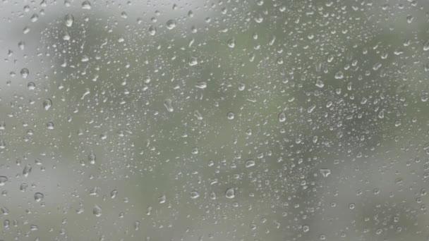 Kapky vody na skle auta zatímco auto pohybuje, déšť pokračoval mimo