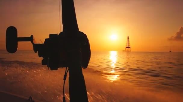 Loď míří od pobřeží na východ slunce