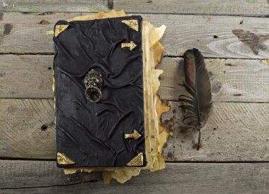 Closed magic book with black quill