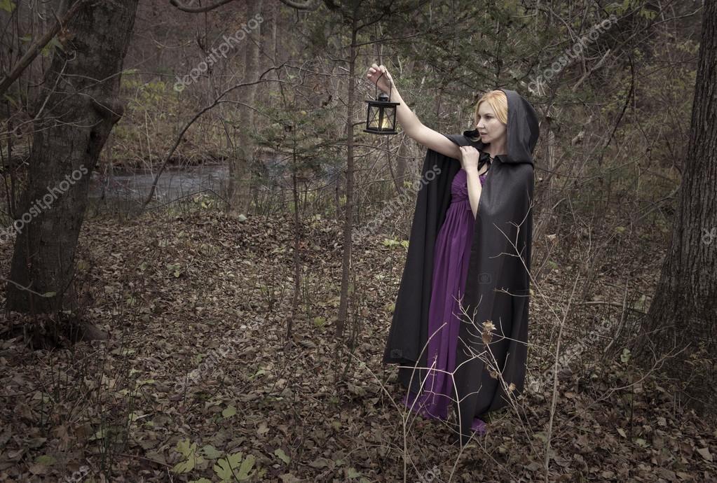lady wearing black mantle in  wood