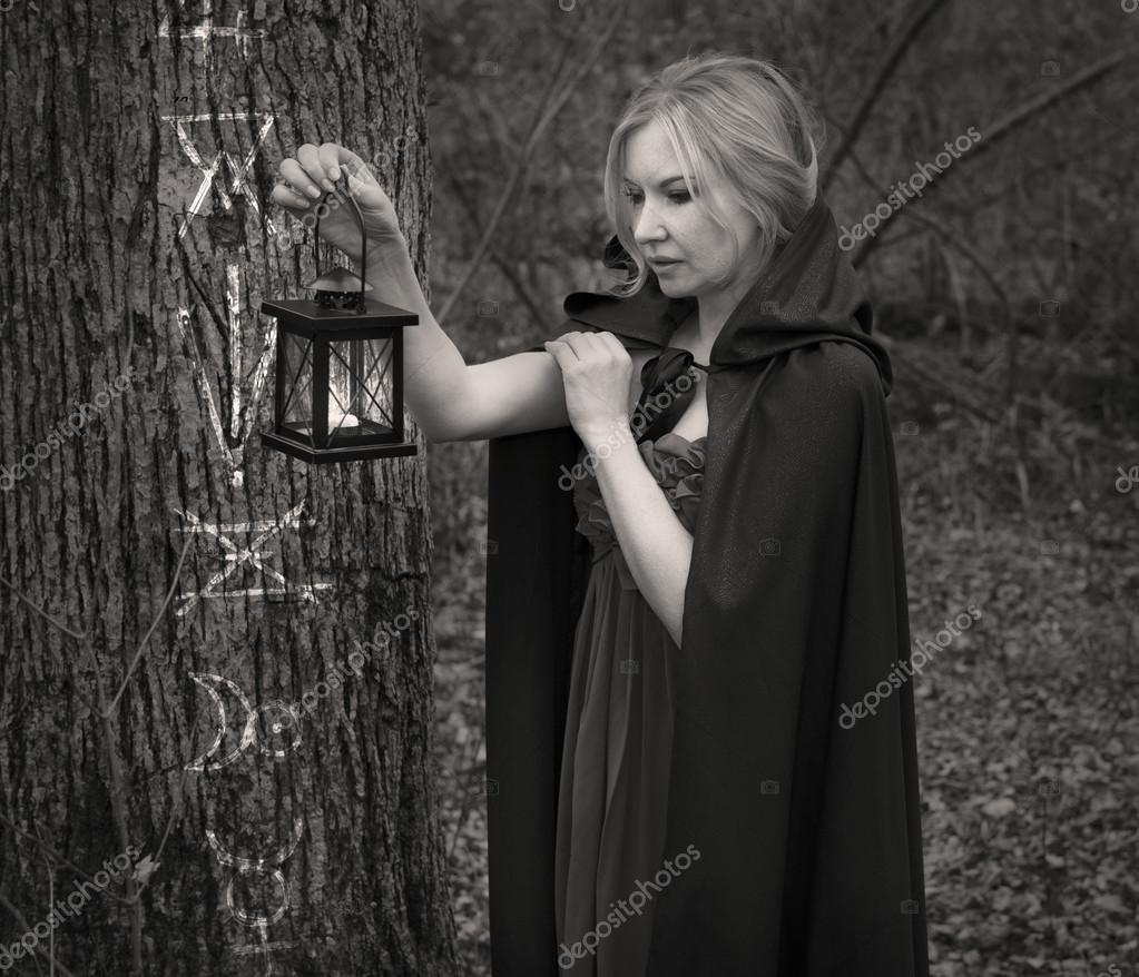 Beautiful witch holding lantern