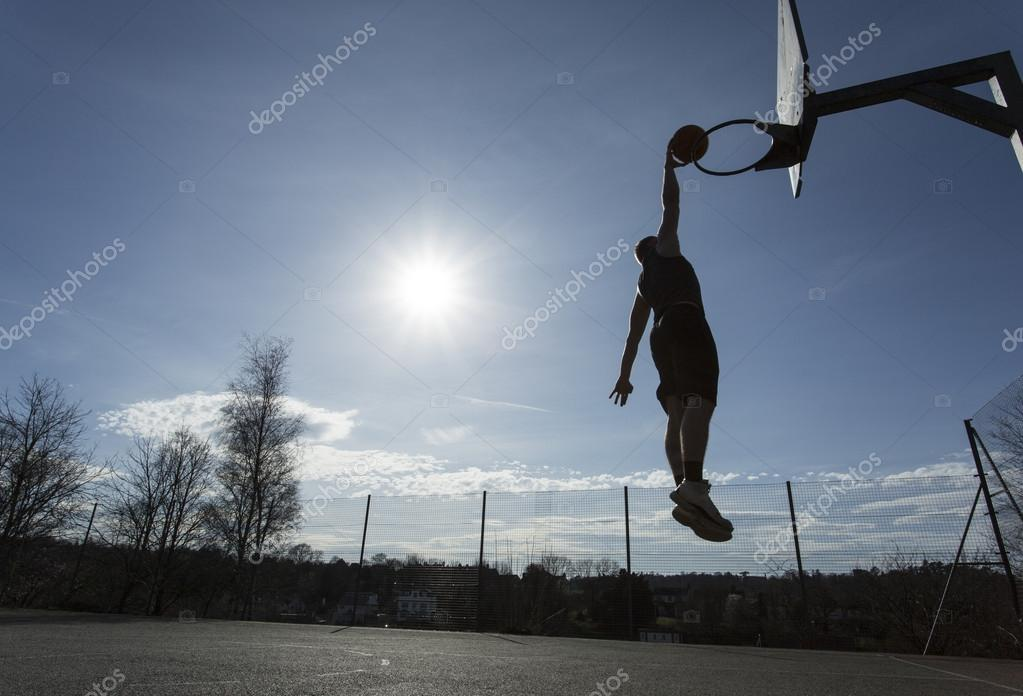 A basketball player silhouette about to slam dunk the ball on an outdoor  court on a bright sunny day — Photo by ... 1b906d71105