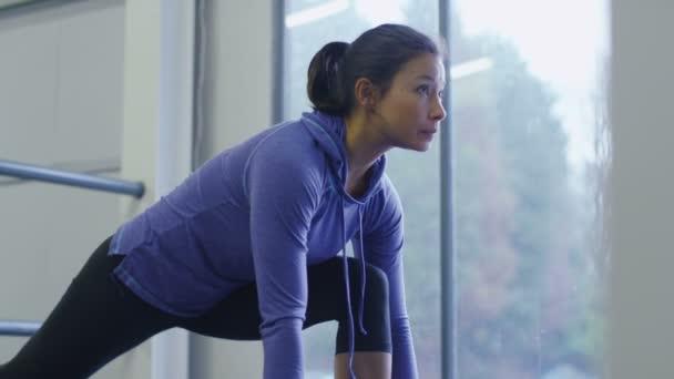 Žena, táhnoucí se v tělocvičně