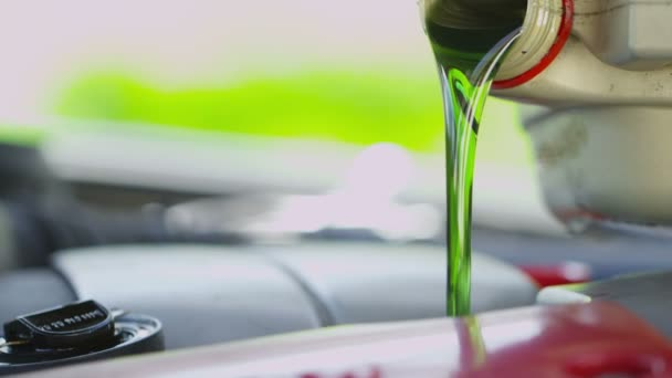 Fresh oil being poured into a car engine in slow motion