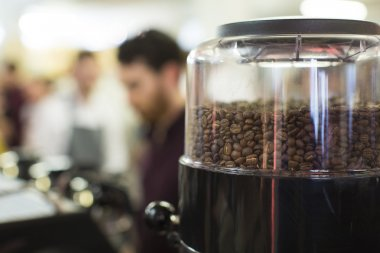 Foreground shallow depth of field of roasted coffee beans in a grinder with blurred activity in the background