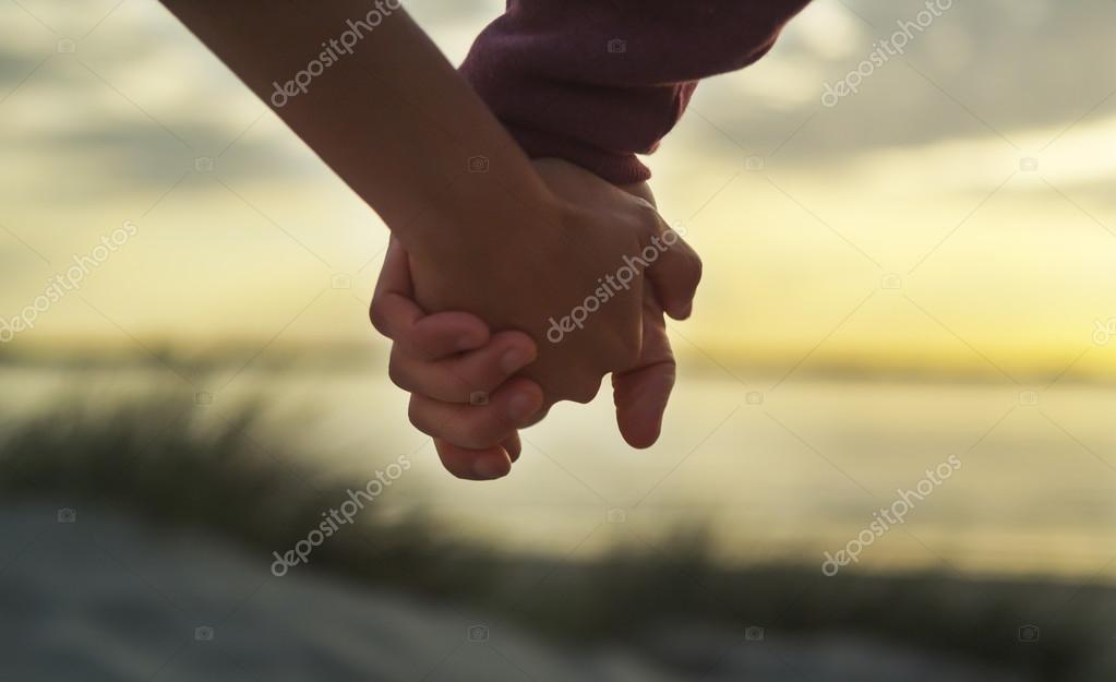 Couple holding hands on a beach at sunset