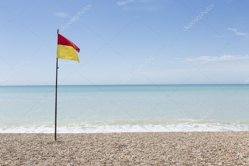 Lifeguard flag on an empty pebble beach on a bright sunny day